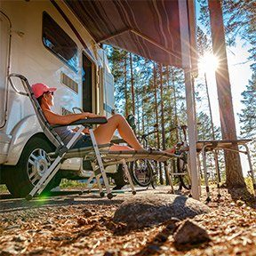 woman lounges beside her recreational vehicle